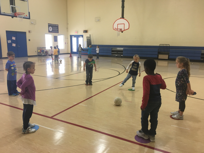 Kindergarten is working on dribbling and passing a soccer ball in small groups this week in PE!