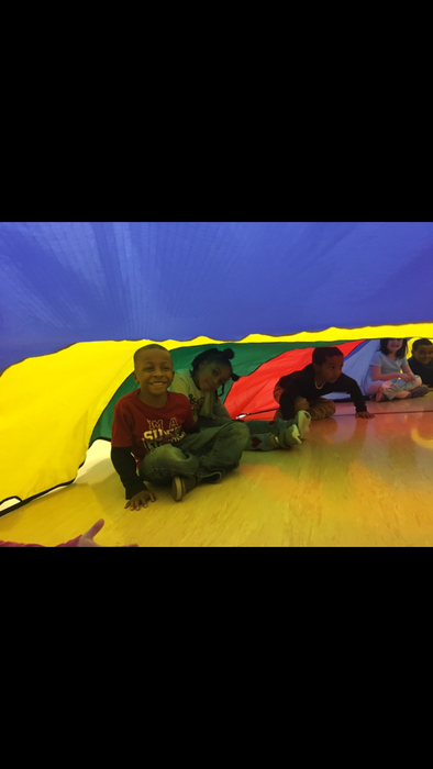 Kindergarten having fun with the parachute